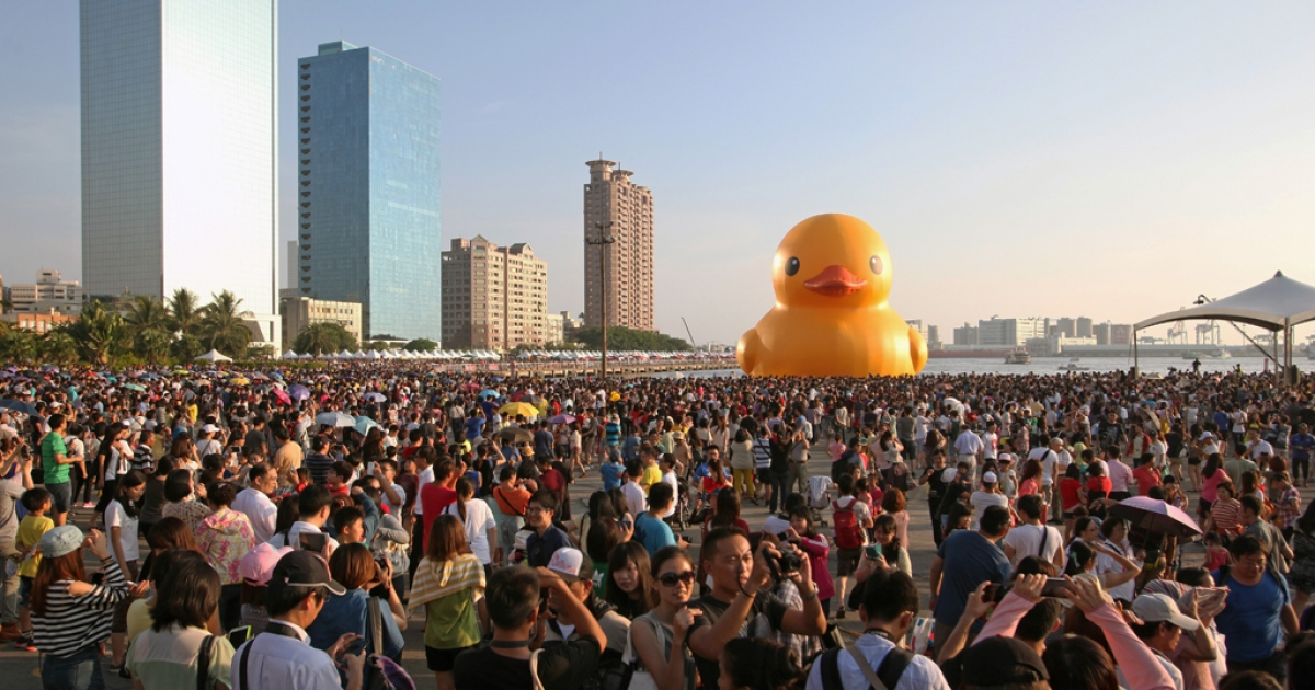 Local residents gather to see Dutch artist Florentijn Hofman's yellow rubber duck (C) at a harbor in the southern city of Kaohsiung on September 19, 2013.</p>