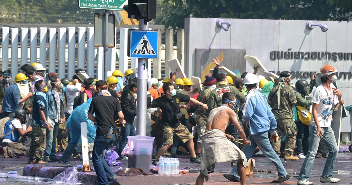 Thai anti government protesters clash with riot policemen during a rally at a stadium to register party-list candidates in Bangkok on December 26, 2013.</p>