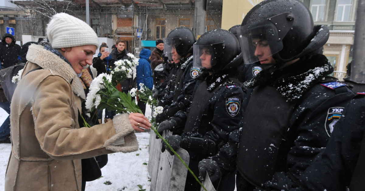 A woman attaches a flower to the shield of a riot policeman blocking the access to Kyiv city center on December 9, 2013.</p>