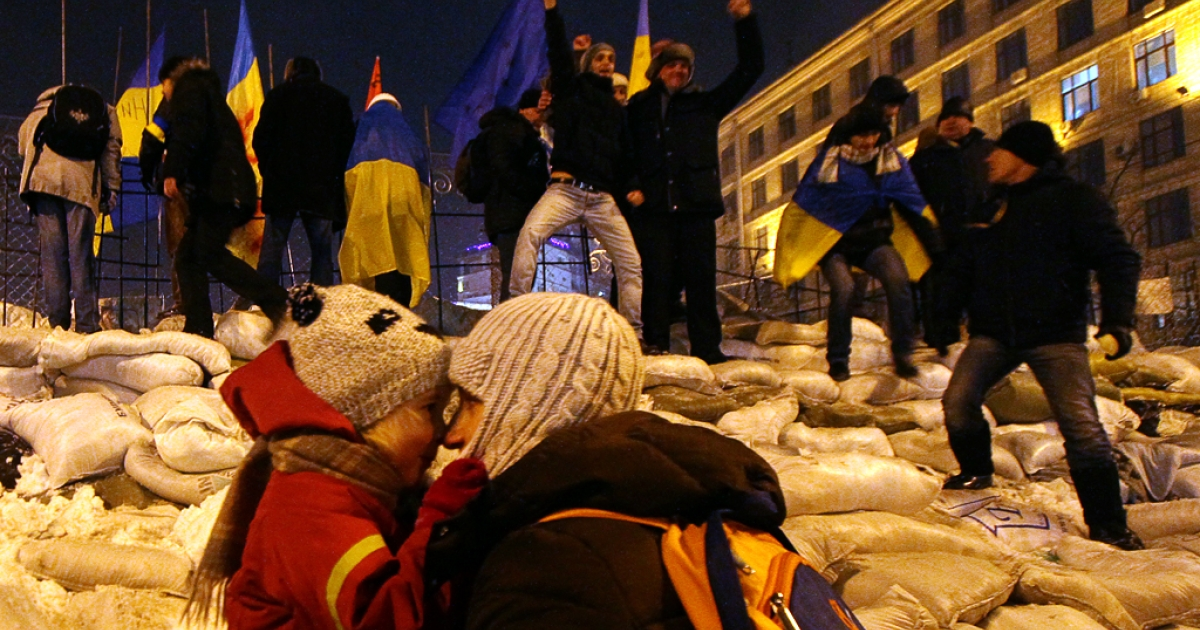 Protesters stand on their newly restored barricade in Kyiv's Independence Square, late on December 11, 2013, destroyed earlier by police during a raid on the protest camp.</p>