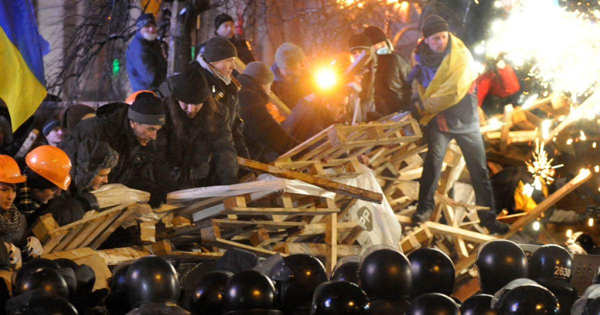 Anti-Yanukovych protesters defend their barricades in front of anti-riot police on Independence Square in Kiev, early on December 11, 2013. Ukrainian security forces pulled out of the epicenter of mass protests in Kiev today after a nine hour standoff with thousands of demonstrators, in a major boost for the opposition to President Viktor Yanukovych.</p>