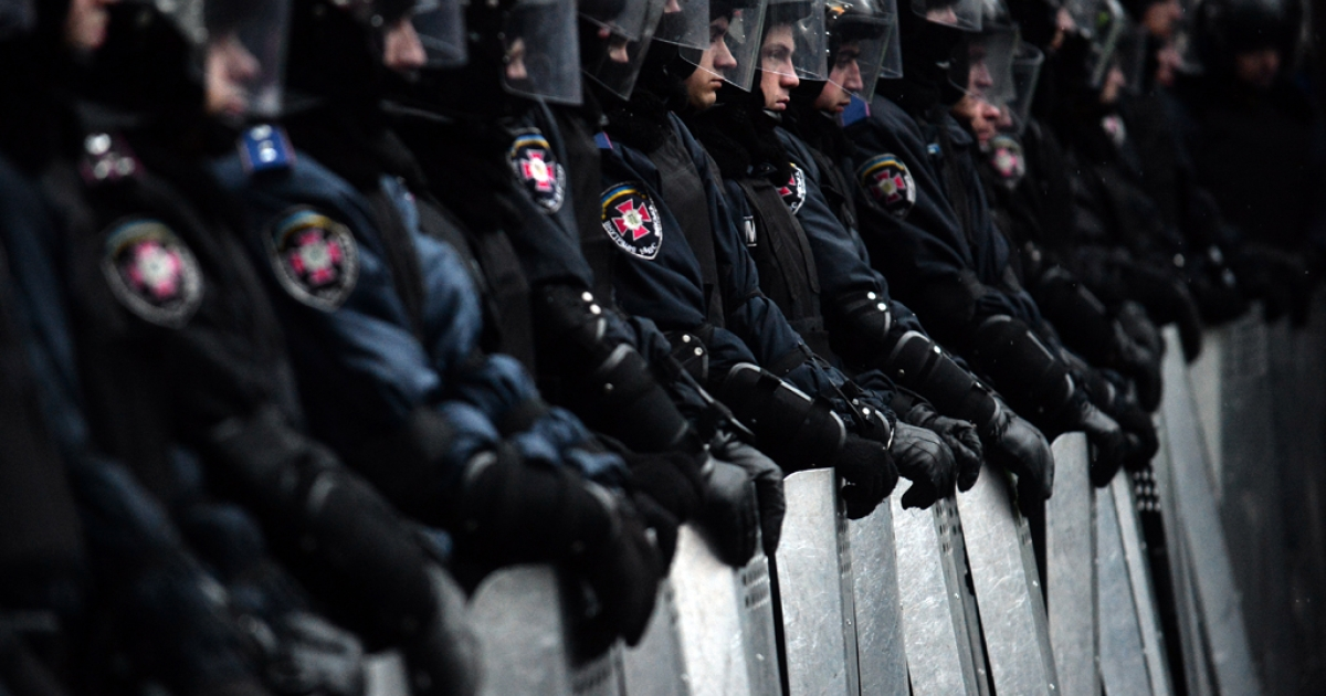 Riot police stand guard in front of Ukrainian parliament after a mass rally called