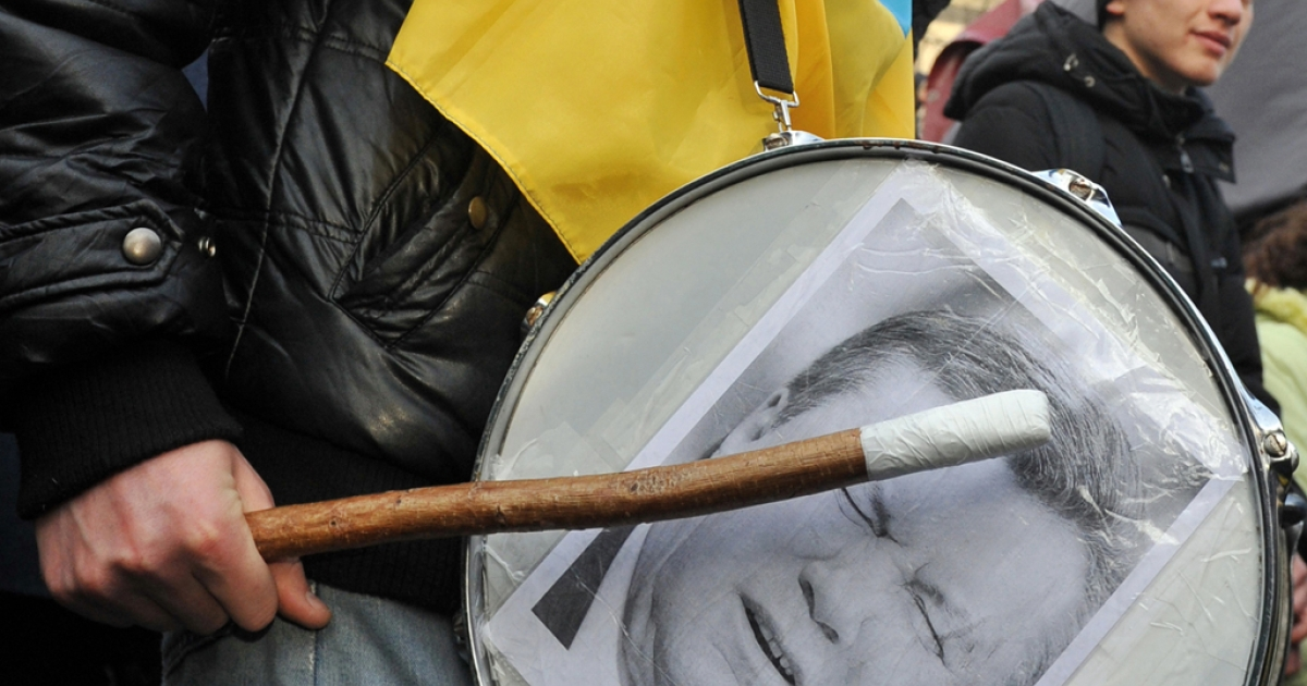 A protester holds a stick over a drum bearing the printed portrait of Ukraine's President Viktor Yanukovych.</p>