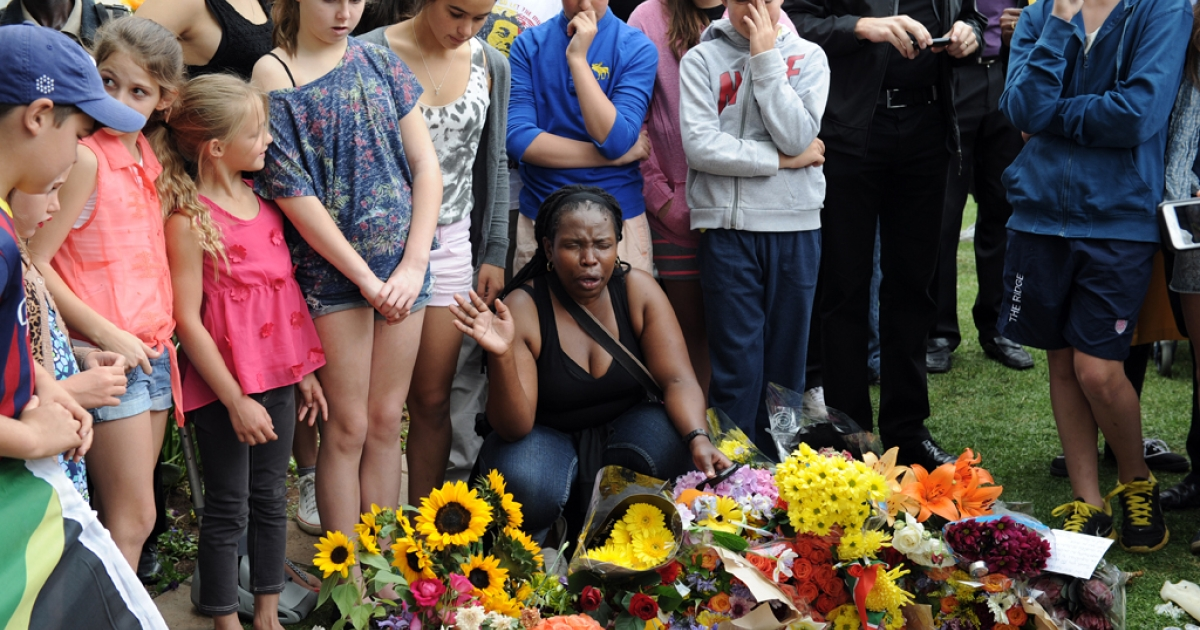 People paying their respects on December 6, 2013 outside the house of former South African President Nelson Mandela in Johannesburg following his death.</p>
