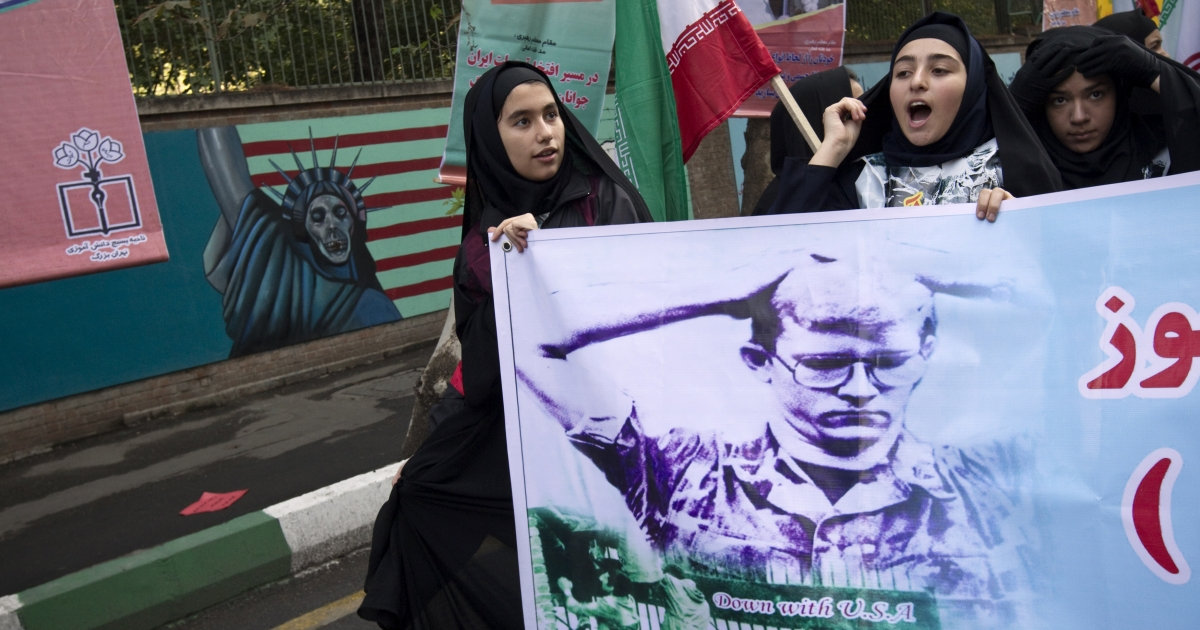 Iranian schoolgirls chant slogans while holding a poster depicting an American hostage during a rally outside the former US embassy in Tehran on November 4, 2010 as they mark the 31st anniversary of the capture of the embassy by Islamist students.</p>
