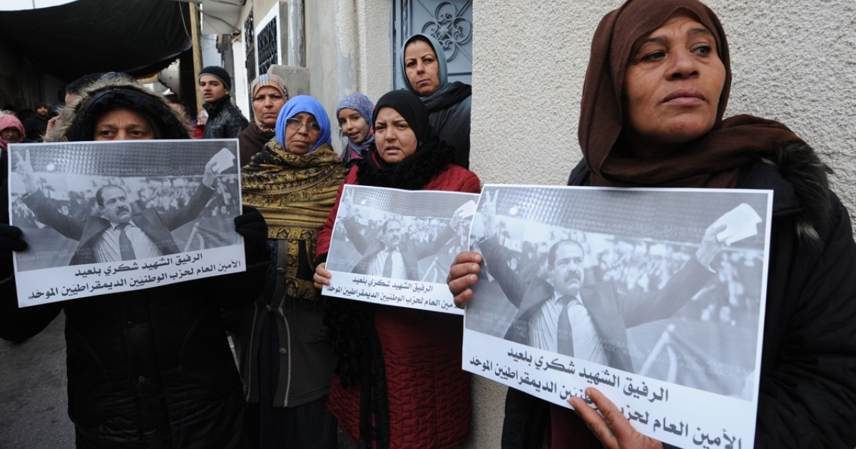 Tunisian women hold placards showing late opposition leader Chokri Belaid before his funeral in Tunis, Feb. 8, 2013.</p>