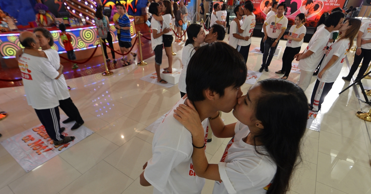 Thai couples kiss during a competition for the 'World's Longest Continous Kiss' ahead of Valentine's Day in Pattaya on February 12, 2013.</p>