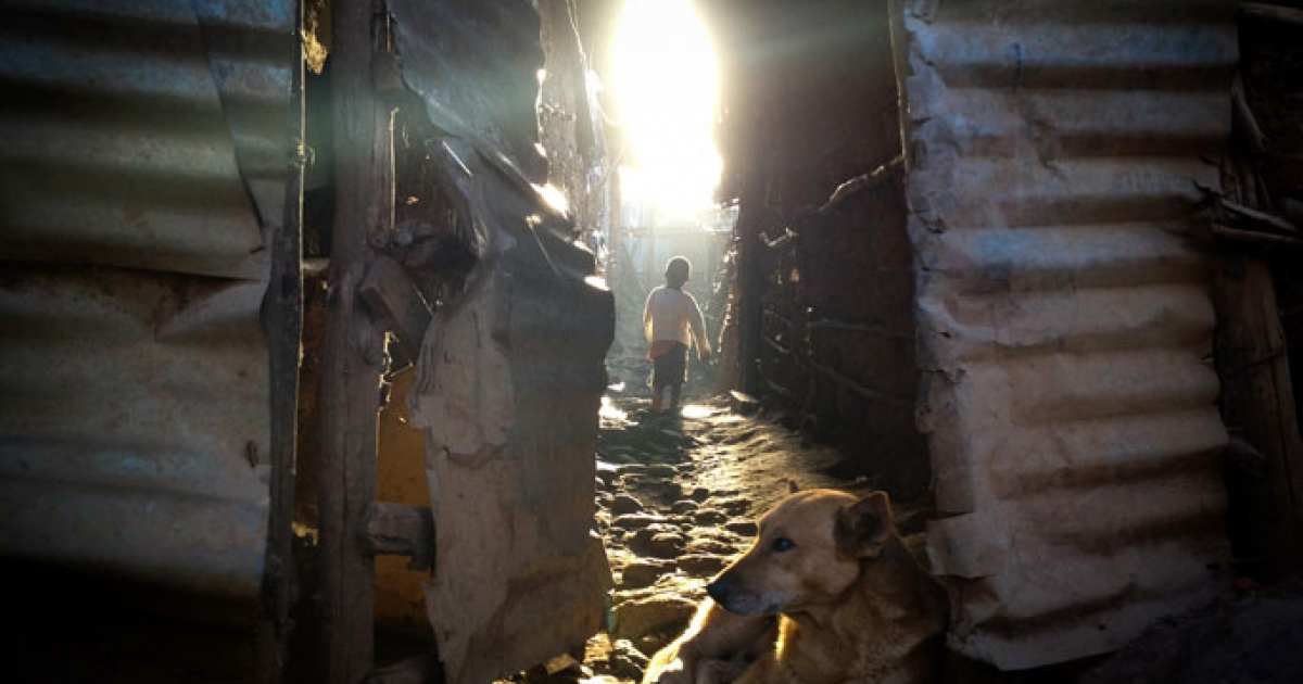 A boy walks outside his home in Kibera at dawn.</p>