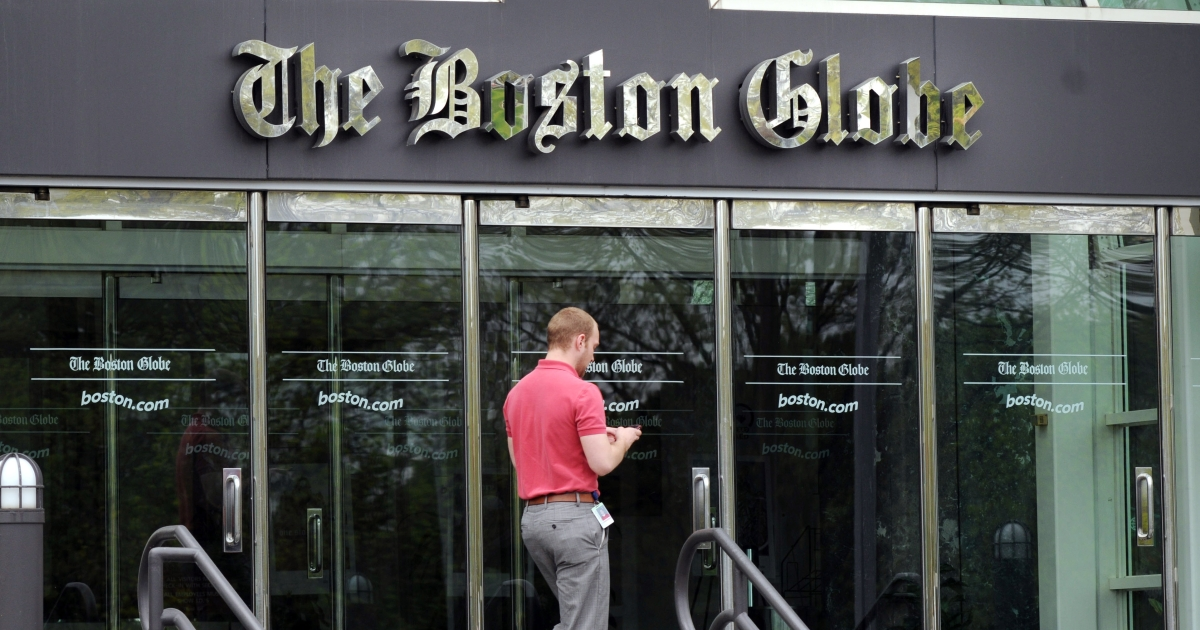 A man walks outside The Boston Globe offices on May 4, 2009 in Dorchester, Massachusetts.</p>