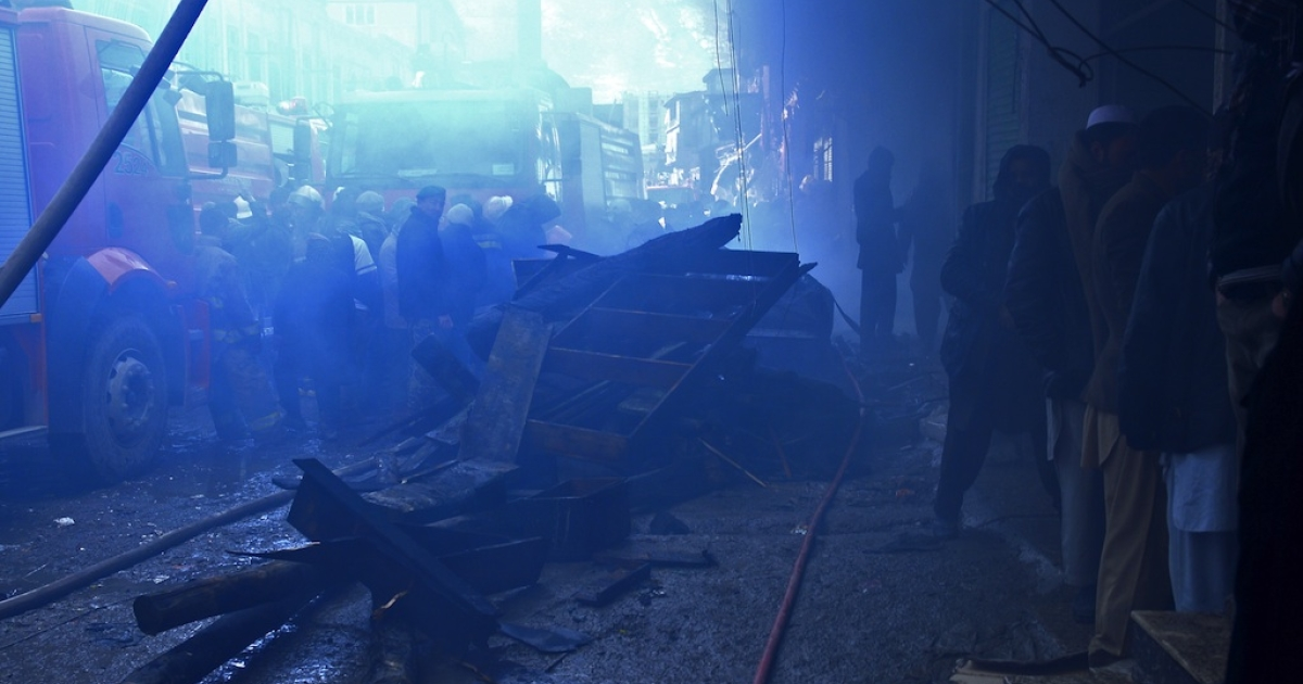 Afghan firefighters attempt to control a fire that swept through a market in Kabul on December 23, 2012. A huge fire swept through a market in downtown Kabul on December 23, destroying hundreds of shops and forcing the city's nearby money exchange to evacuate, police and witnesses said.</p>