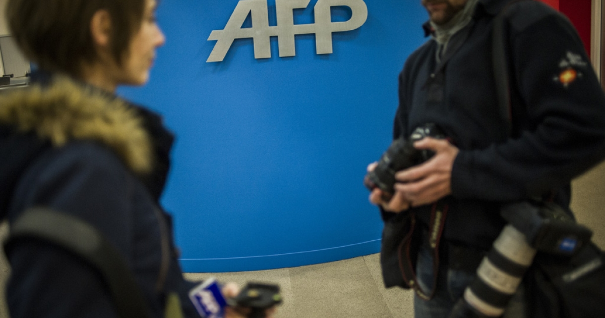 Journalists arrive at the Agence France Presse headquarters in Paris on January 4, 2013.</p>