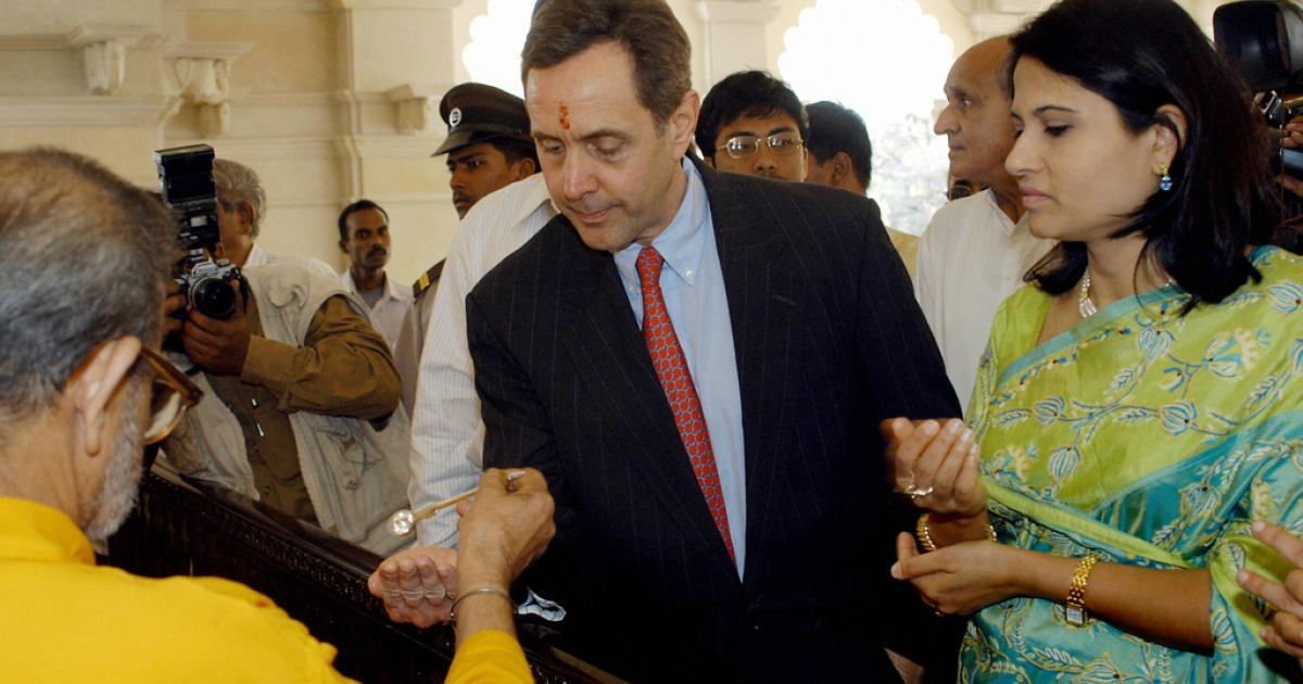 The great-grandson of Henry Ford, founder of the Ford Motor Company, Alfred B. Ford (C) watched by his wife Sharmila takes 'Prasad' (sacred food) from a Hindu priest after he offered prayers at the newly build Sri Mahalaxmi Temple in Calcutta, February 20, 2004.</p>