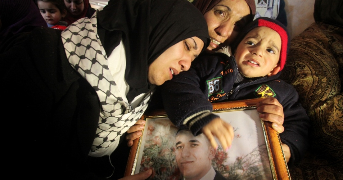 The sisters of Arafat Jaradat (picture), a Palestinian inmate who died in an Israeli prison, mourn their brother's death while embracing his son Muhannad during his funeral in the West Bank village of Saair on February 25, 2013.</p>