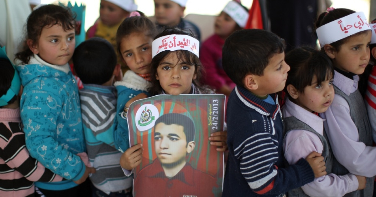 A Palestinian girl carries a poster of Arafat Jaradat, who died in an Israeli prison.</p>