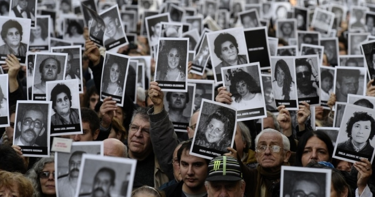 People hold portraits of victims of the terrorist bombing attack against the Argentine-Israeli Mutual Society (AMIA) institute that killed 85 people and injured 300, during the commemoration of its 18th anniversary, in Buenos Aires on July 18, 2012.</p>