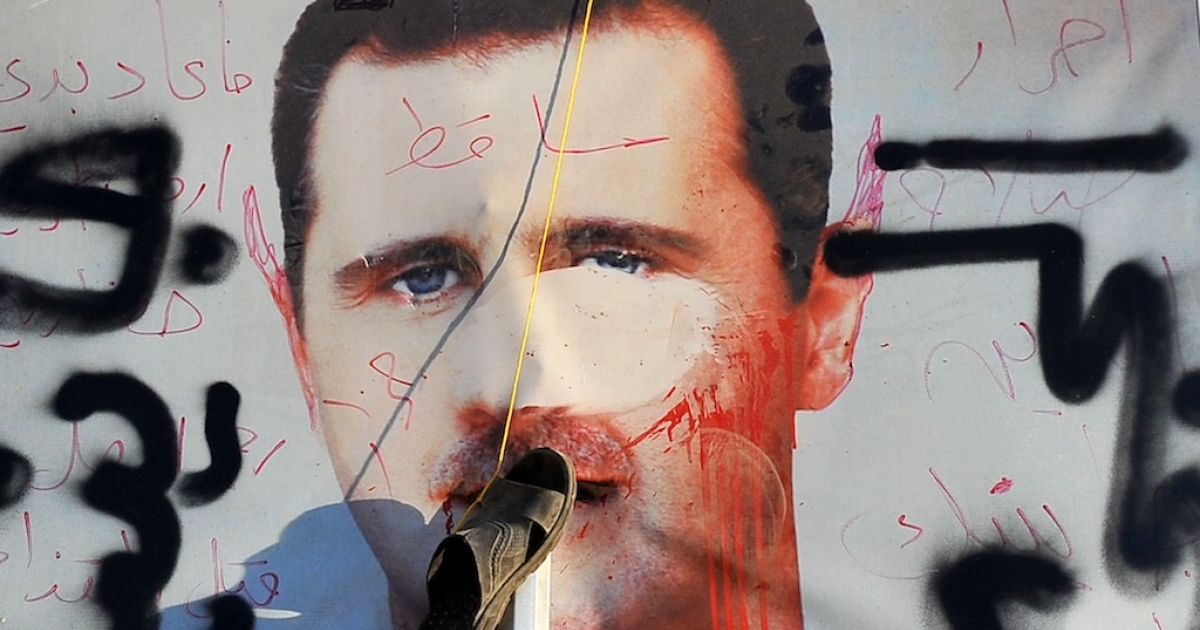 A slipper hangs on a vandalised poster of Syrian President Bashar al-Assad in Aleppo on July 24, 2012.</p>