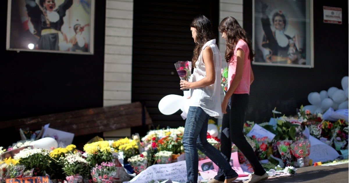 Friends and family lay flowers outside the nightclub in Brazil where more than 230 young people perished in a fire.</p>