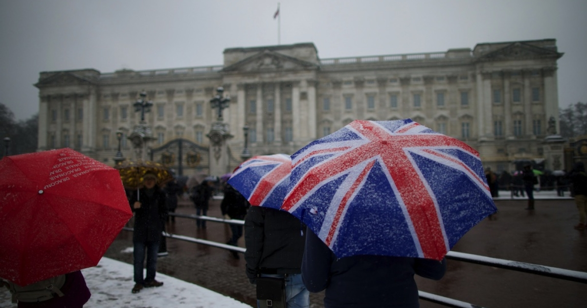 Tourists gather in front of Buckingham Palace during snowfall in central London on January 20, 2013.</p>