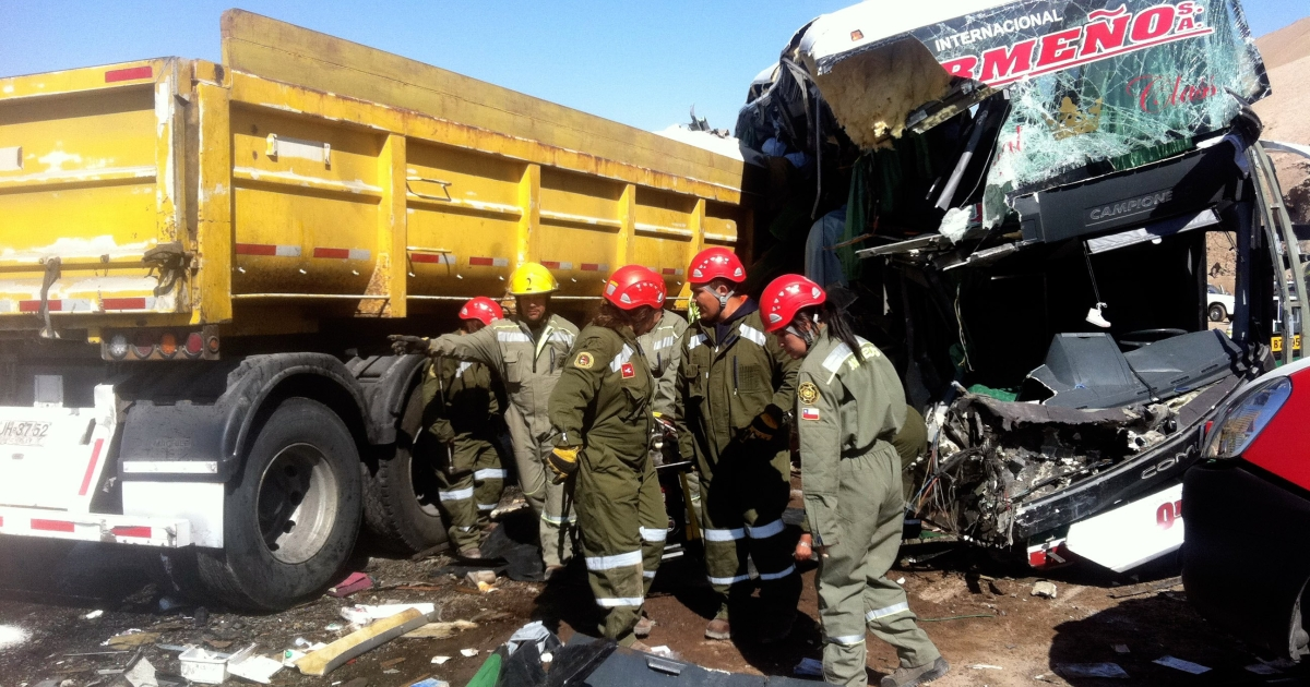 Rescuers work on November 5, 2012 on the wreckage of a bus that collided with a lorry on Route 5 North in Antofagasta, 1400 km north of Santiago killing at least six Peruvian nationals.</p>