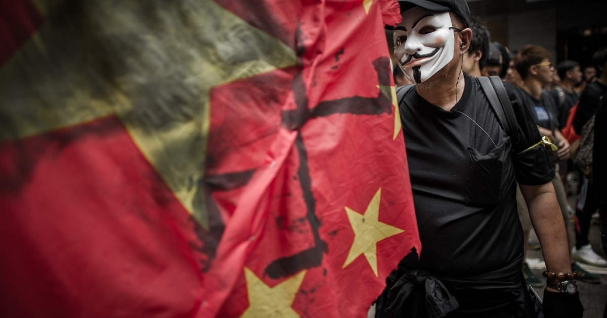 A man wears a mask of the Anonymous hacker group as he and other people take part in a protest for the cause of late Chinese dissident Li Wangyang in Hong Kong on June 10, 2012. Li, 62, who spent 22 years in jail for his role in the Tiananmen democracy protests died in allegedly suspicious circumstances in his hospital ward in central China's Hunan province on June 6 by his sister and brother-in-law.</p>