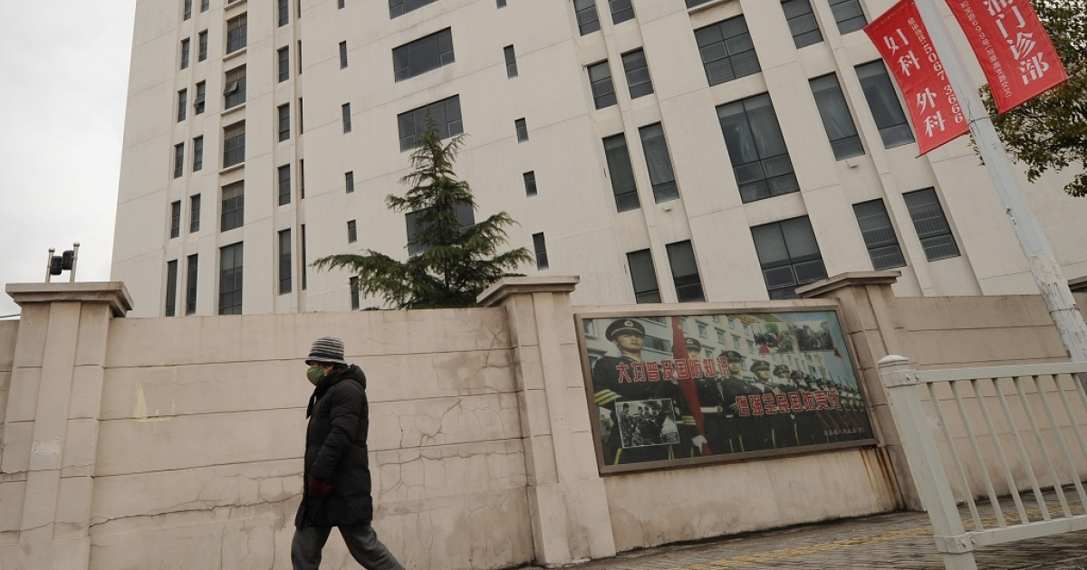 A person walks past a 12-storey building alleged in a report on February 19, 2013 by the Internet security firm Mandiant as the home of a Chinese military-led hacking group after the firm reportedly traced a host of cyberattacks to the building in Shanghai's northern suburb of Gaoqiao. Mandiant said its hundreds of investigations showed that groups hacking into US newspapers, government agencies, and companies 'are based primarily in China and that the Chinese government is aware of them.</p>