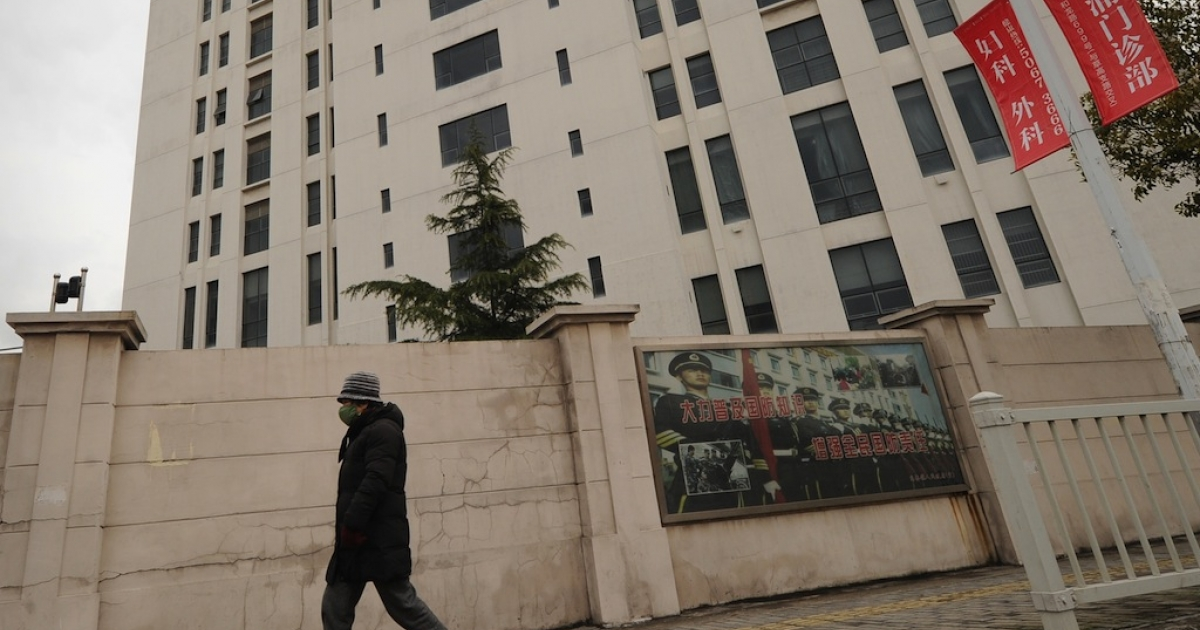 A person walks past a 12-story building alleged in a report by the Internet security firm Mandiant to be the home of a Chinese military-led hacking group on Feb. 19, 2013.</p>