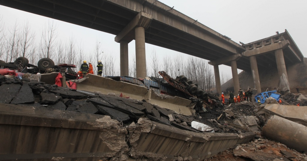 Rescuers work at the scene of the collapsed Yichang bridge near the city of Sanmenxia, in central China's Henan province, on February 1, 2013.</p>
