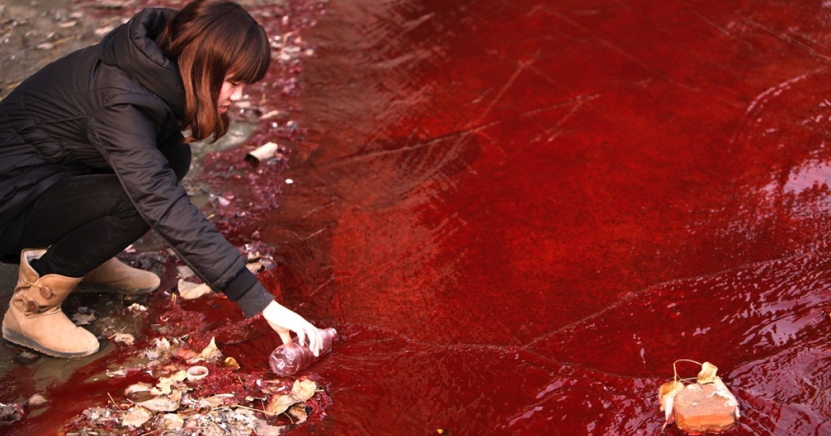 A woman collects a sample of the red polluted water flowing from a sewer into the Jian River in Luoyang, north China's Henan province on Dec. 13, 2011.</p>