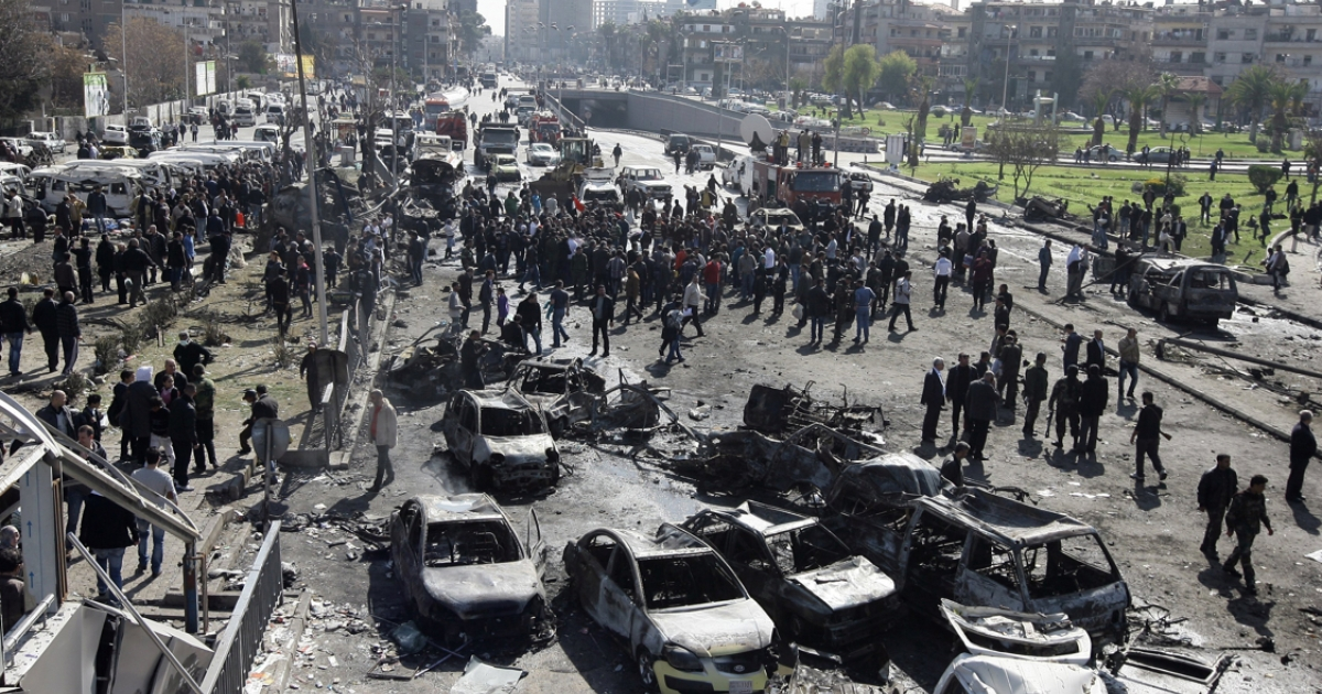 A general view shows burnt cars at the scene of a powerful car bomb explosion near the headquarters of Syria's ruling Baath party in the centre of Damascus on February 21, 2013. The blast sent thick smoke billowing across the capital's skyline, killing dozens of people and causing widespread destruction.</p>