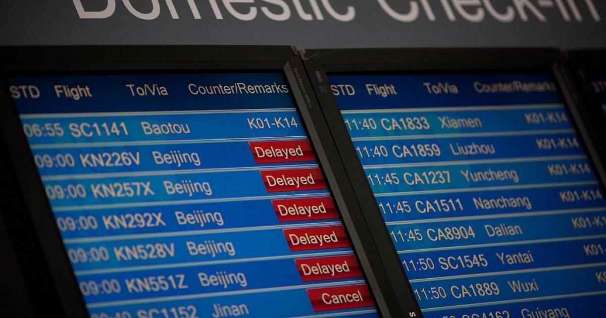 A domestic departures board shows flight delays. (Ed Jones/AFP/Getty Images</p>