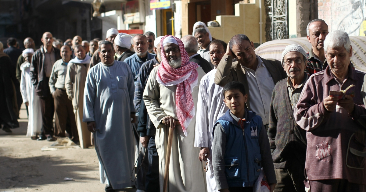 Egyptian men queue outside a polling station during a referendum in Giza, south of Cairo, on Dec. 22, 2012.</p>