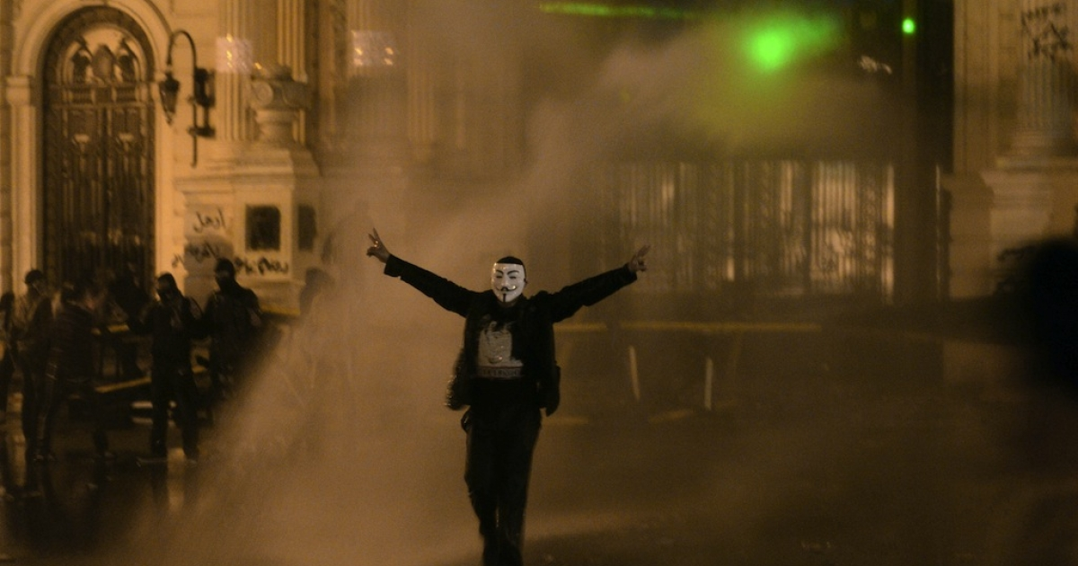 A protestor wearing a Guy Fawkes mask is sprayed as Egyptian security use water cannons to disperse anti-government protestors throwing stones into the grounds of the al-Kobaa Presidential palace in Cairo, on Feb. 15, 2013.</p>