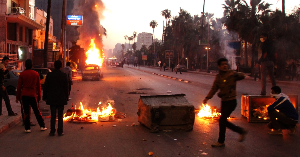 Egyptian anti-government protestors take cover behind burning dust bins during clashes with riot police following a demonstration against Egypt's President and the Muslim Brotherhood in the northern coastal city of Alexandria on February 8, 2013. Thousands took to the streets across Egypt after opposition groups called for 'Friday of dignity' rallies demanding Egyptian President Mohamed Morsi fulfill the goals of the revolt that brought him to power.</p>