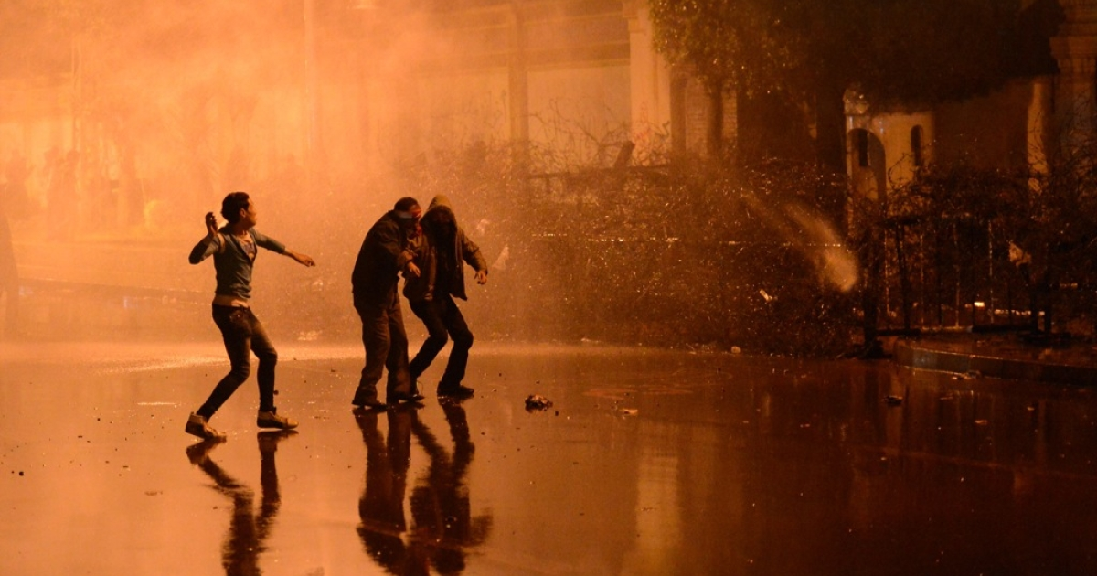 Egyptian security use water cannon as protesters throw stones into the grounds of the presidential palace in Cairo on Feb. 11, 2013, as the opposition held rallies to mark the second anniversary of former president Hosni Mubarak's overthrow.</p>