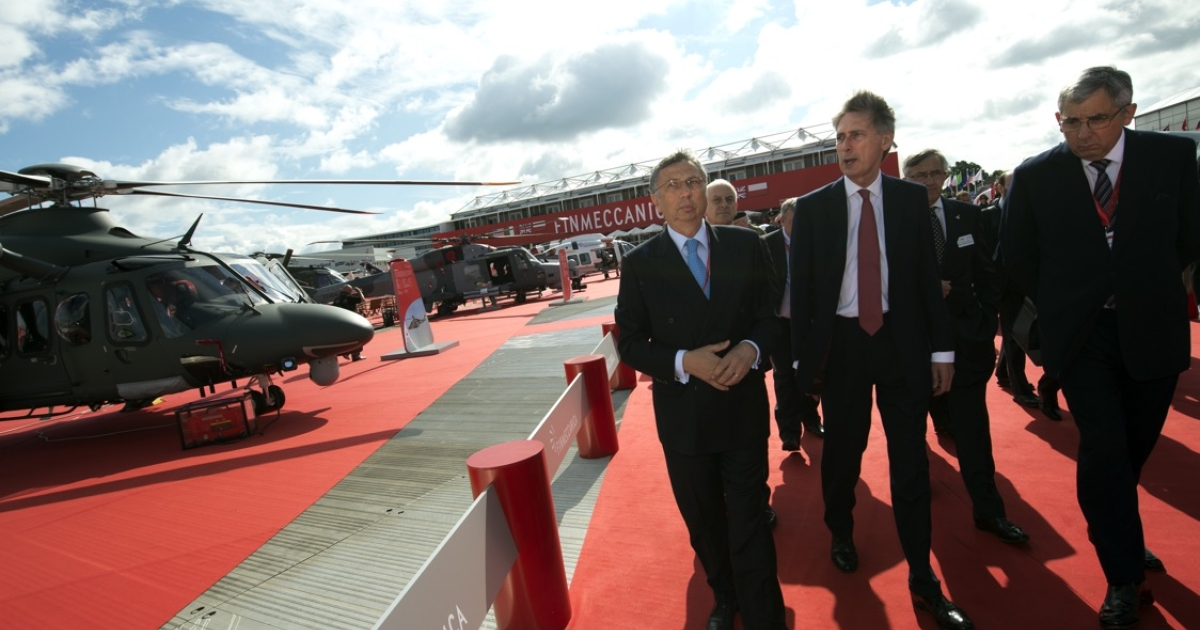 Giuseppe Orsi (L), president and CEO of Finmeccanica, shows US Secretary of State for Defence Philip Hammond around Finmeccanica's stand at the Farnborough International Airshow in Hampshire, southern England, on July 11, 2012. Orsi has since been arrested for alleged corruption.</p>