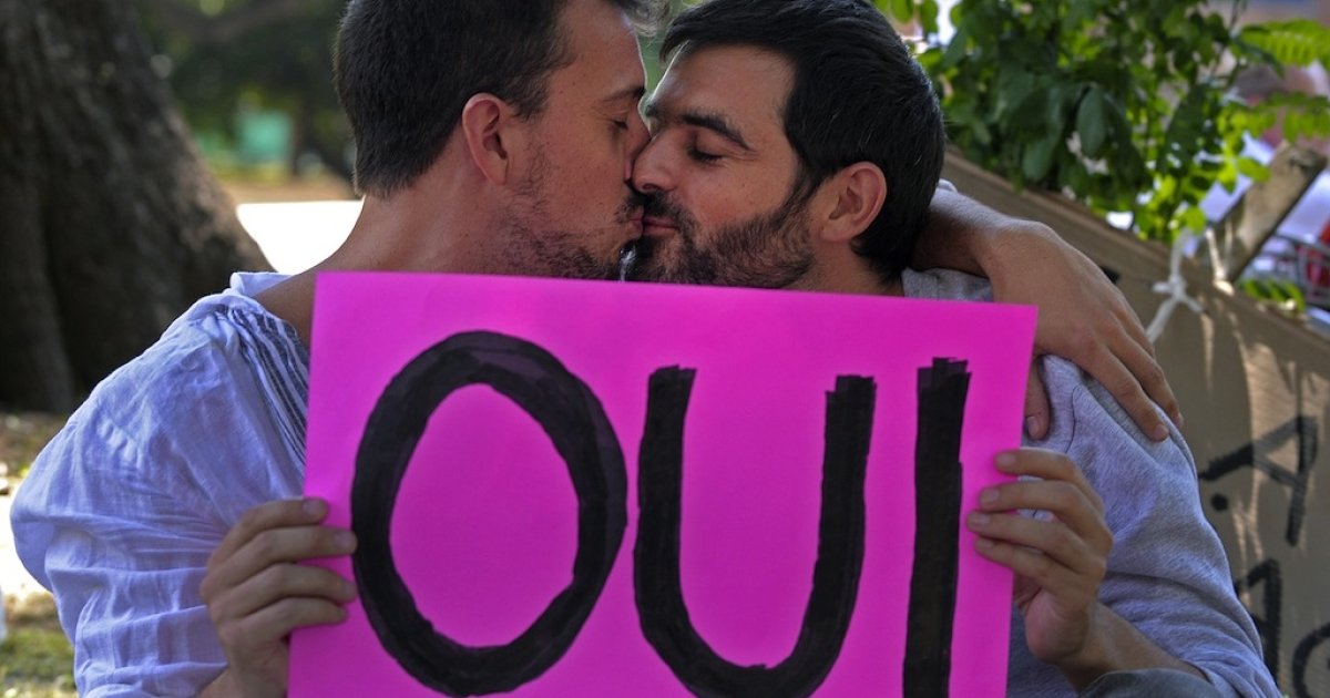 Two men kiss during a demonstration in support of the legalisation of gay marriage and LGBT parenting in France at the Plaza Francia in Buenos Aires, on Jan. 27, 2013.</p>