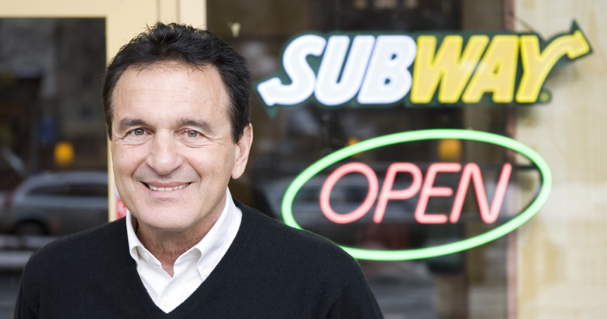 Fred DeLuca, president and founder of sandwich maker Subway, poses during an interview in front of a Subway restaurant at