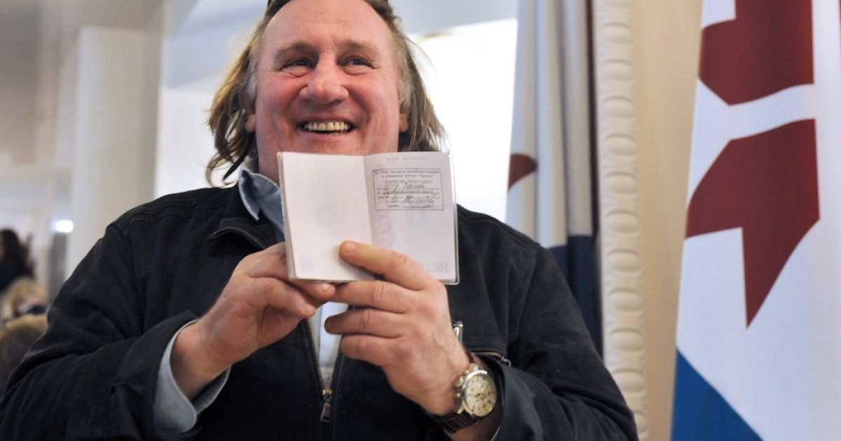 French actor Gerard Depardieu (C) holds his passport registration at the theatre in Saransk, Russia on February 23, 2013. Depardieu, who was granted a Russian passport by President Vladimir Putin after complaining about high tax rates in France.</p>
