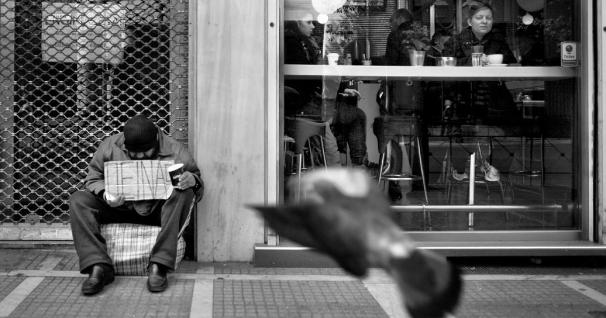 An unemployed man in central Athens holds a cardboard sign saying