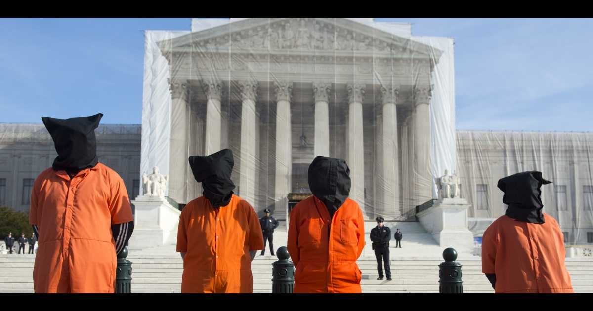 Protesters wear prison jump suits and hoods during an anti-Guantanamo Bay military prison demonstration in front of the US Supreme Court in Washington, DC, on Jan. 8, 2013.</p>