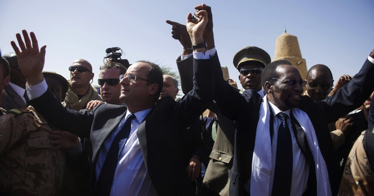 France's President Francois Hollande (L) flanked by Mali's interim president Dioncounda Traore (R), wave as Hollande arrives at the airport of Timbuktu, the second step of his one-day visit in Mali, on February 2, 2013. Islamists had torched the building housing priceless ancient manuscripts as they fled the town.</p>