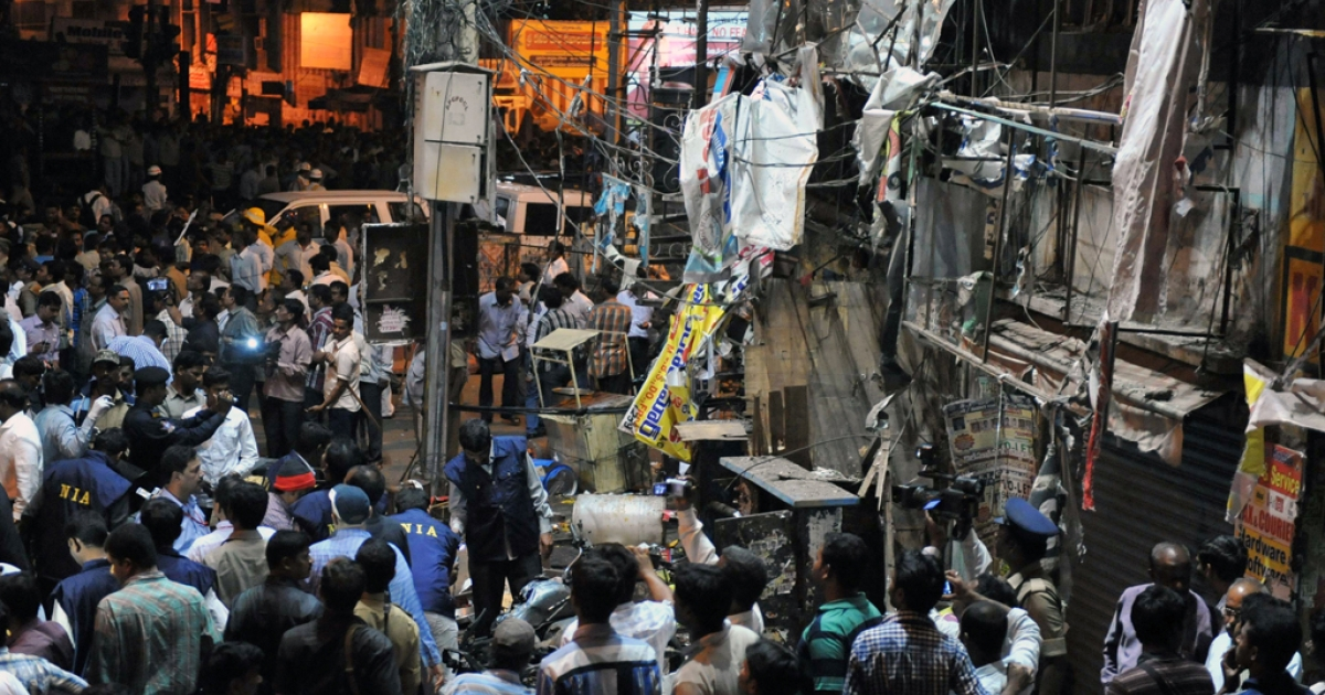 Indian authorities and onlookers are pictured at the site of a bomb blast at Dilshuk Nagar in Hyderabad on February 21, 2013.  At least 18 people were killed and 52 wounded when bombs ripped through crowded areas of the Indian city of Hyderabad on Thursday in what the prime minister called a