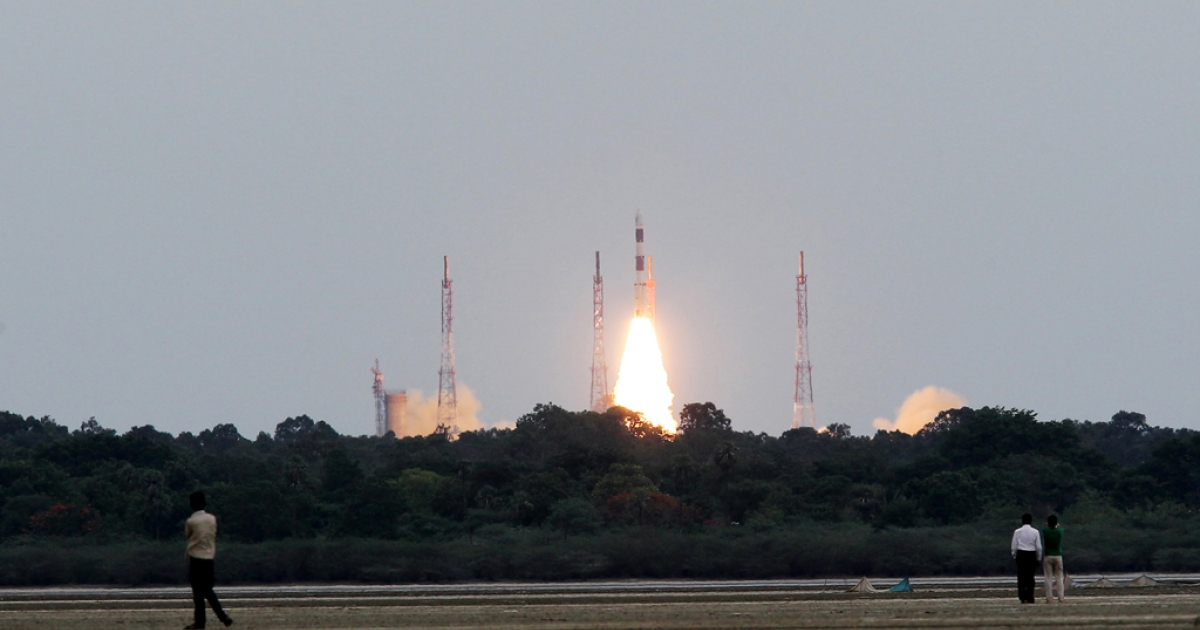 People in a field watch as an Indian communication satellite GSAT-12 onboard a Polar Satellite Launch Vehicle PSLV C-17 blasts off from the spaceport in Sriharikota on July 15, 2011.</p>