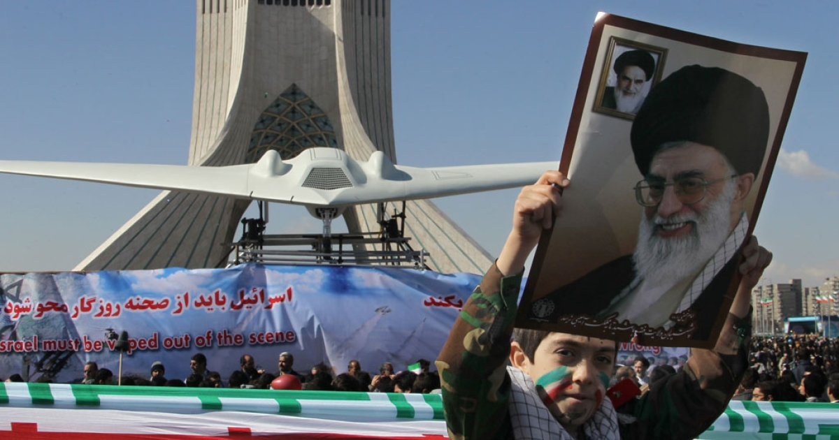 An Iranian boy holds a portrait of supreme leader Ayatollah Ali khamenei as he walks past a replica of the captured US RQ-170 drone on display next to the Azadi (Freedom) tower during the 33rd anniversary of the Islamic revolution in Tehran on February 11, 2012.</p>
