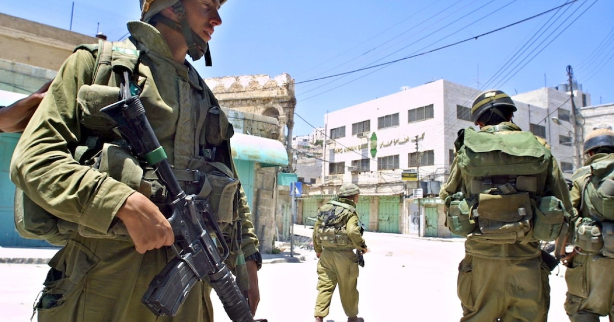 Israeli soldiers patrol the empty streets of Hebron on June 26, 2002, in the West Bank.</p>