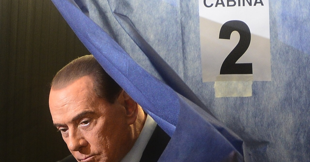 Italian former Prime Minister Silvio Berlusconi exists a voting booth at a polling station on Feb. 24, 2013 in Milan.</p>