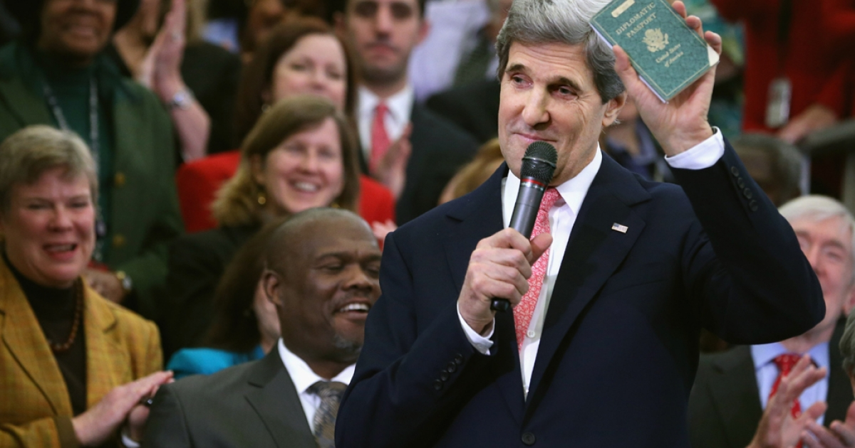 US Secretary of State John Kerry holds up his first diplomatic passport he received as an 11-year-old boy while making remarks to employees on his first day at the State Department on Feb. 4, 2013, in Washington, DC.</p>