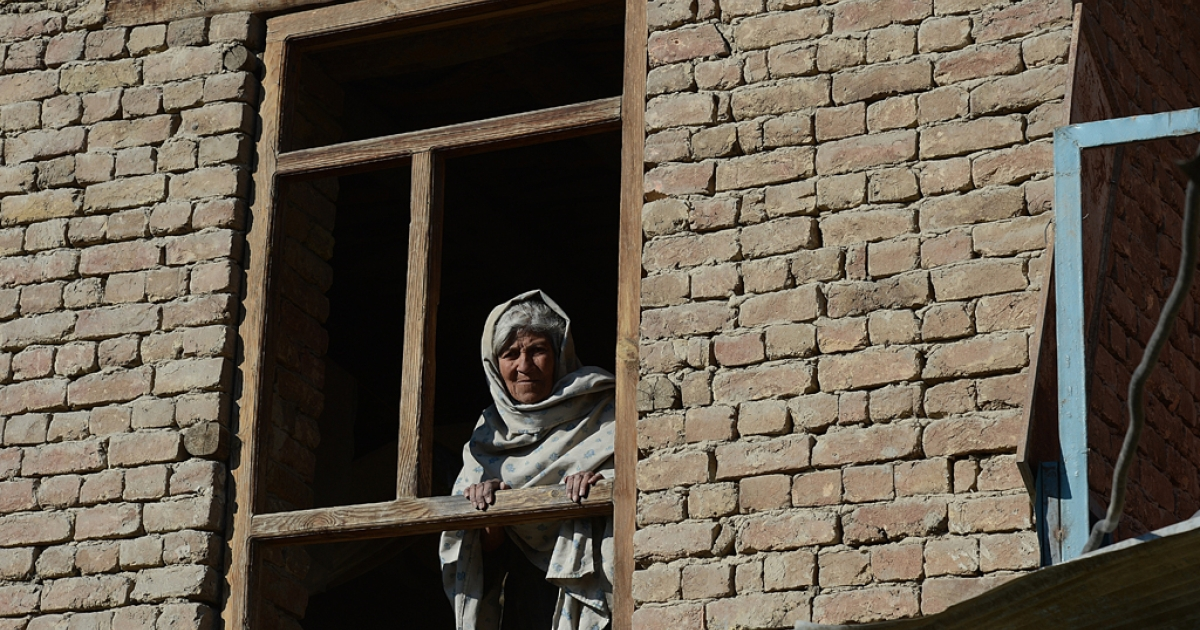 An elderly Afghan woman looks through the window of her house after a clash between Afghanistan forces and Taliban fighters in Kabul on Jan. 21, 2013. As the US and allies focus on fighting in the countryside, parts of the Afghan capital have slipped unnoticed into lawlessness.</p>