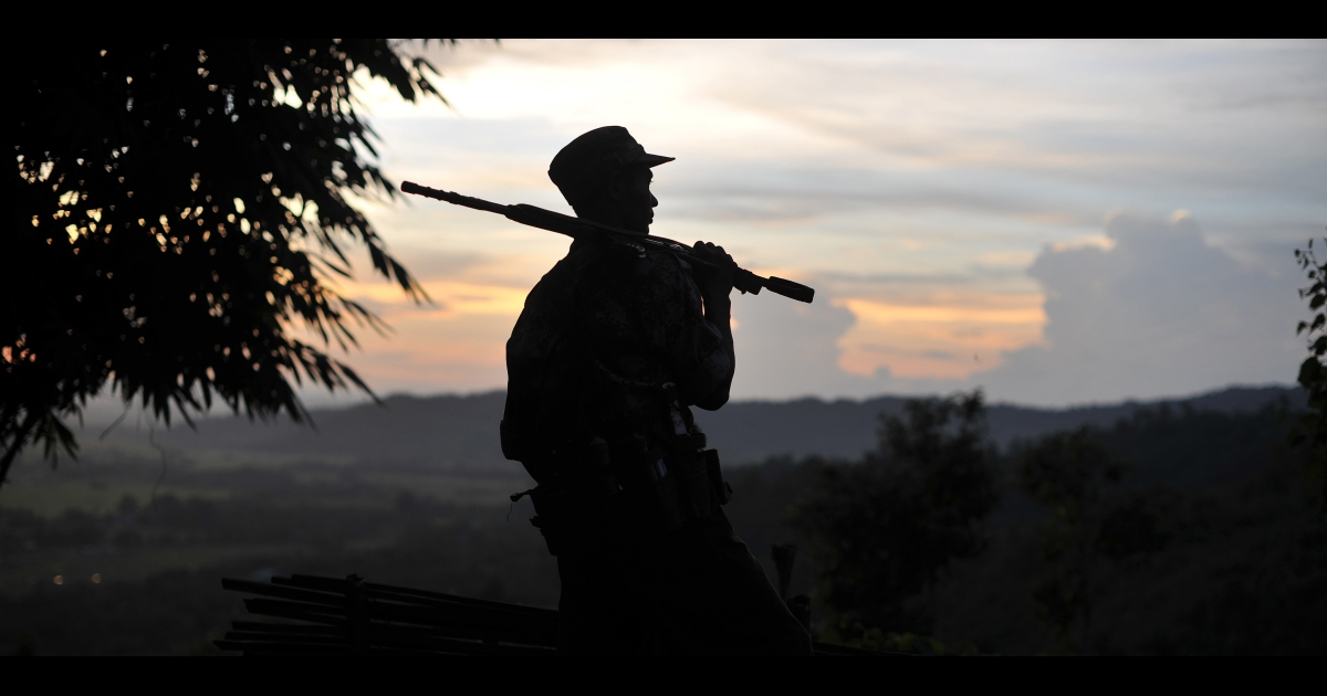A soldier from the All Burma Students Democratic Front - Northern Burma (ABSDF-NB), an ally of the Kachin Independence Army (KIA), holds his weapon as he looks out from an outpost on the Laja Yang front-line in Myanmar's northern Kachin state, home to the ethnic Kachin rebels' headquarters.</p>