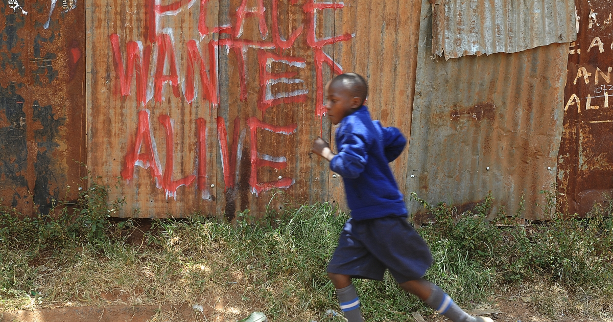 A schoolboy runs past a message urging for peaceful polls on Monday.</p>
